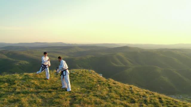 ws pov two men training taekwondo with double mitt on the edge of mountain plateau / vipava, nature park nanos, slovenia - taekwondo stock videos & royalty-free footage