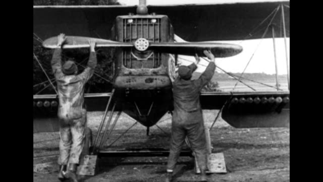 two men turn plane propellers by hand to get it started / cplane flies with automatic pilot / cu of the plane's mechanicals / various early biplanes... - glenn h. curtiss stock videos and b-roll footage