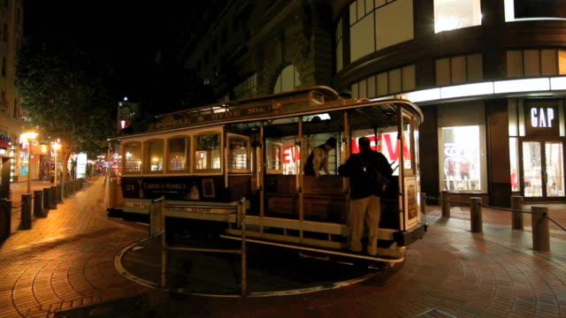 vídeos de stock, filmes e b-roll de ws two men turning cable car at terminus, powell street at night, san francisco, california, usa - cable