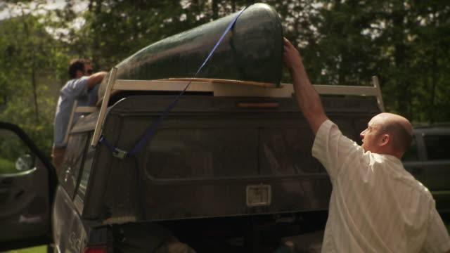 cu two men tying canoe on top of pick up truck, morristown, vermont, usa - tunnhårig bildbanksvideor och videomaterial från bakom kulisserna