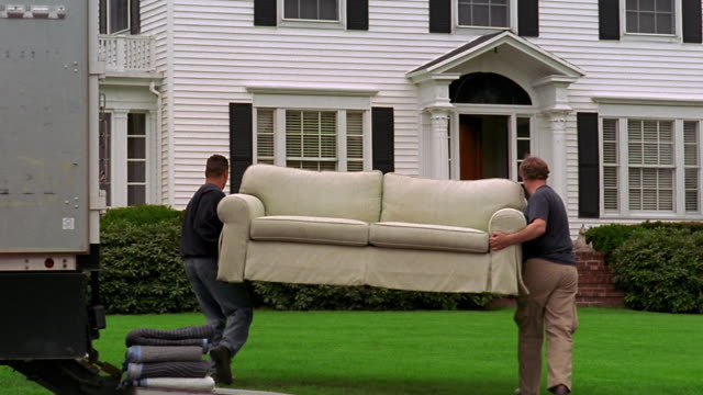 Two men unloading couch from moving truck + walking towards house