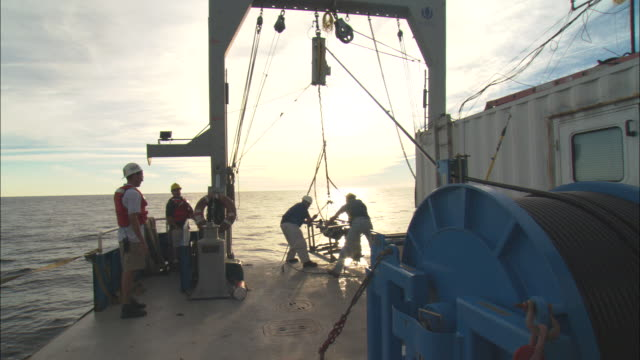 two men use a crane to lift a submersible onto the deck of a ship. - research stock videos & royalty-free footage