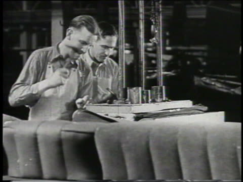 vidéos et rushes de b/w 1932 two men use hammers on ford factory assembly line - ford