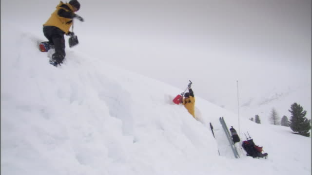 stockvideo's en b-roll-footage met two men use shovels to move snow on a slope. - men