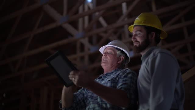 CU LA Two men using a digital tablet at a building site