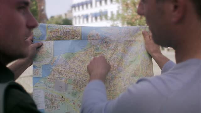 Two men using a map Skane Sweden.