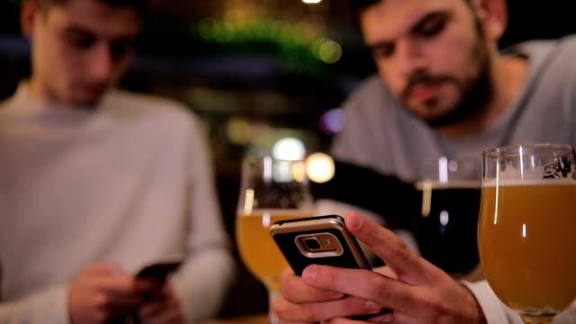 stockvideo's en b-roll-footage met twee mannen met behulp van slimme telefoons in pub - men