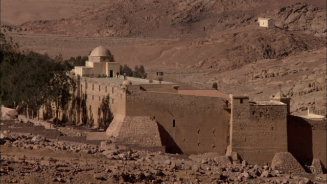 Two men walk along the rooftop of Saint Catherine's Monastery in Mount Sinai Egypt. Available in HD.