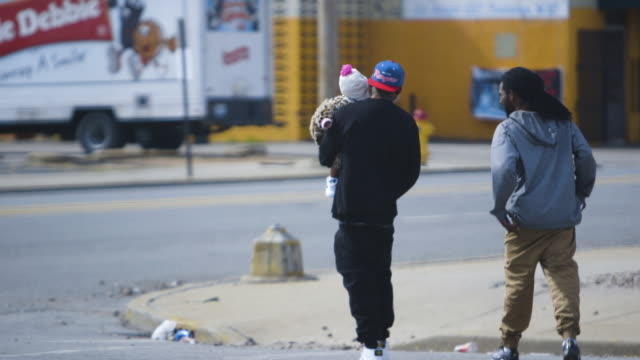 two men walk on street with baby, wide shot - missouri stock videos and b-roll footage