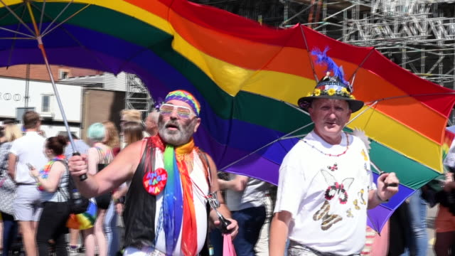 Two men walk under and 2person umbrella decorated with pride colours in the Gay Pride Parade 2017 in slow motion