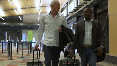 vídeos de stock, filmes e b-roll de two men walking at an airport with suitcases - mala de rodinhas