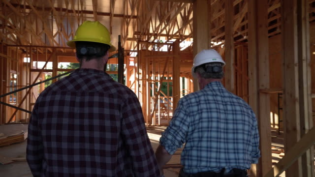 MS RV TS Two men walking through a building under construction