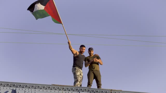 two men wave a palestinian flag atop a bridge as people participate in a pro-palestinian rally on may 31, 2021 in the bronx borough of new york city.... - campaigner stock videos & royalty-free footage