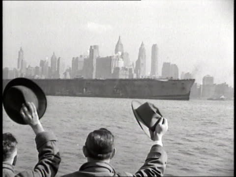 Two men wave their hats at the burned ocean liner SS Normandie near New York City