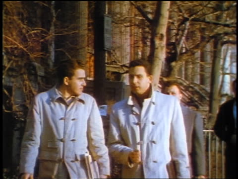 1957 two men wearing identical coats walking on city sidewalk / feature - 1957 stock-videos und b-roll-filmmaterial
