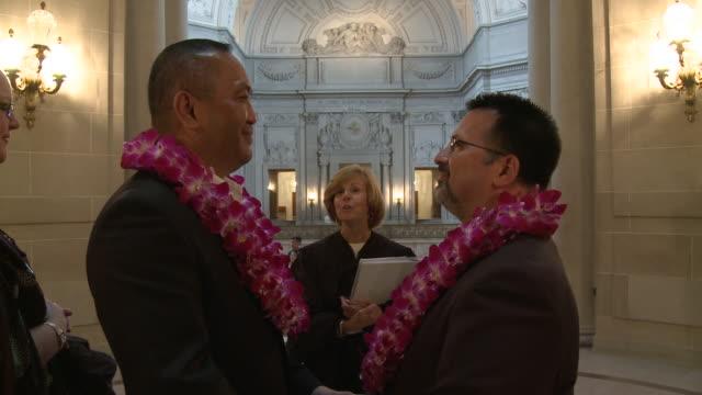 two men wearing leis during their wedding at san francisco city hall/ san francisco, california/ audio - ゴーティー点の映像素材/bロール