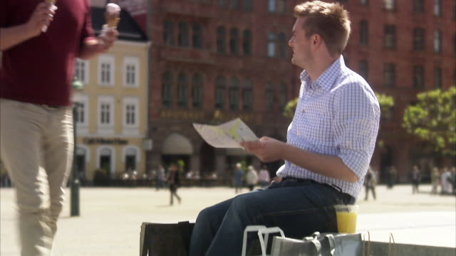 Two men with a map and  ice-cream cones Malmo Skane Sweden.