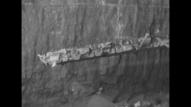 vídeos y material grabado en eventos de stock de two men with a very long drill digging into and then removing it from the lower wall of coal / a huge saw with jagged metal teeth turns sideways and... - coal mine