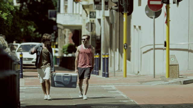two men with coll box on street - cool box stock videos & royalty-free footage