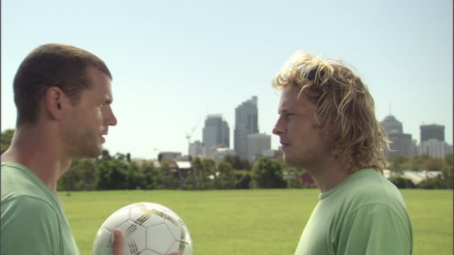 CU, Two men with football standing face to face in park, Sydney, Australia