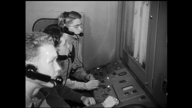 two men with headsets monitoring machine; man repairing machine; men working on wall full of wires and cables; men mounting satellite/radar onto a... - man and machine stock videos & royalty-free footage