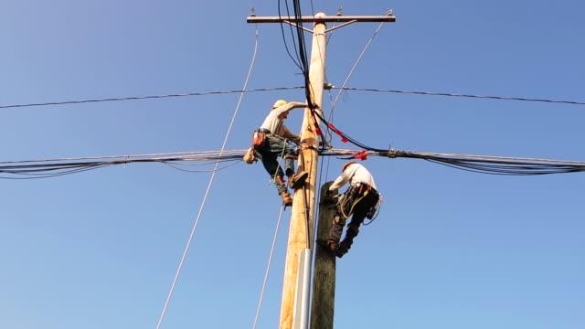 vídeos y material grabado en eventos de stock de two men work on power line - poste telegráfico