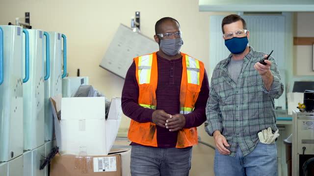 stockvideo's en b-roll-footage met twee mensen die in drukinstallatie werken, die gezichtsmaskers dragen - drukker