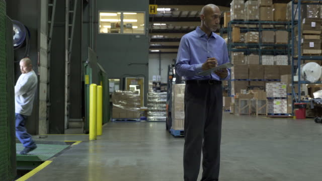 two men working in warehouse, stocktaking and pulling pallet by hand - pacific islander background stock videos & royalty-free footage