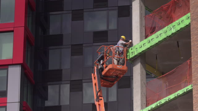 two men working on brooklyn building exterior using cherry picker on a sunny day. - cherry picker stock videos & royalty-free footage
