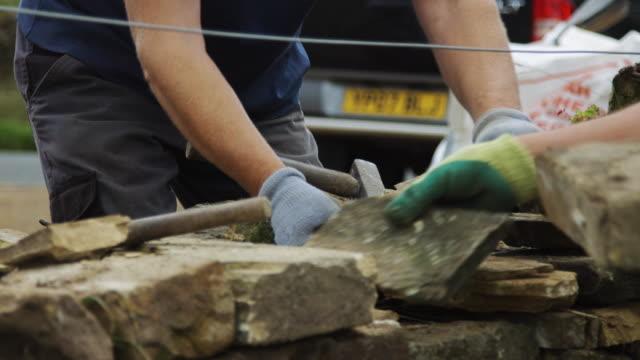 ドライに取り組んでいる 2 人の男性の石壁