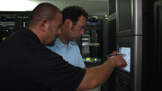 two men working on monitor in server room - netzwerkadministrator stock-videos und b-roll-filmmaterial
