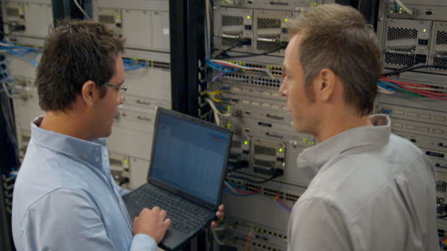 ms two men working on network server, sydney, australia - complessità video stock e b–roll