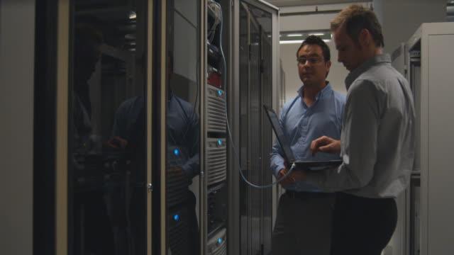 MS ZI Two men working on server in server room, Sydney, Australia