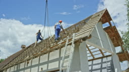 Two men working on the roof of a building