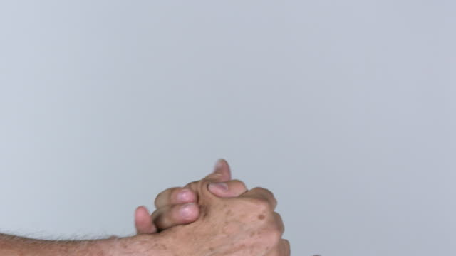 Two men wraparound hand shaking as one pats fists