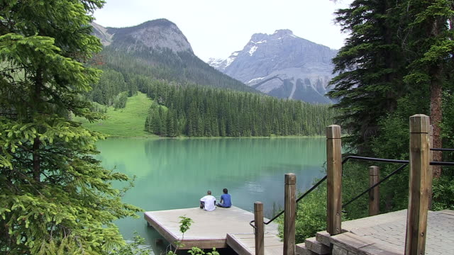 MS Two mens sitting on small wooden dock at Emerald Lake / Yoho Nationalpark, British Columbia, Canada