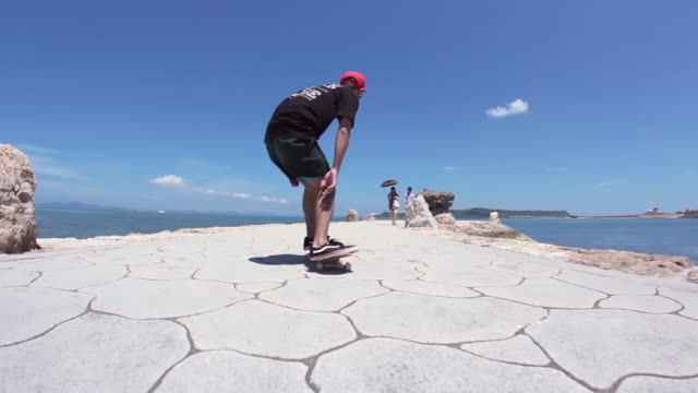 MS POV Two men's skateboarding on side walk near beach area, showing stunts / Uruma, Okinawa, Japan