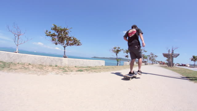 ms pov two men's skateboarding on side walk near beach area / uruma, okinawa, japan - ビデオカメラ点の映像素材/bロール