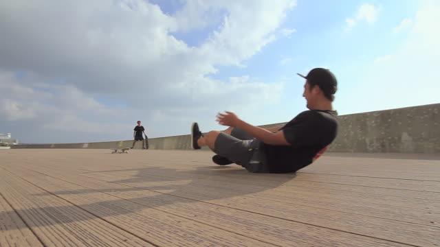 WS PAN Two men's skateboarding on side walk, one is fallen down / Chatan, Okinawa, Japan