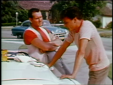 vídeos y material grabado en eventos de stock de 1963 two men/teens leaning against car talking / one pulls out money + shows it to other - sólo hombres jóvenes