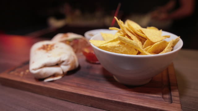 two mexican steak burritos with potato chips and sauce in bowl on wooden board in pub - crunchy stock videos & royalty-free footage