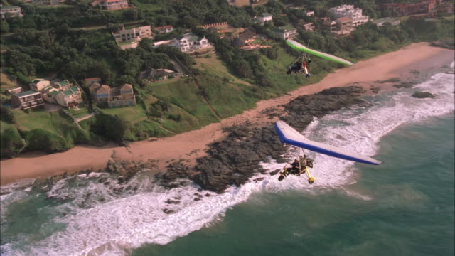 Two microlights fly over sea with beach and coastal residences in background, South Africa Available in HD.
