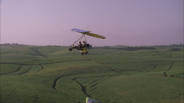 Two microlights fly over sugar cane fields, Kwazulu Natal, South Africa Available in HD.