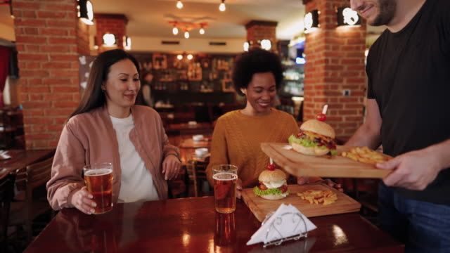 two mid adult women enjoy beer and burgers in pub - female friendship stock videos & royalty-free footage