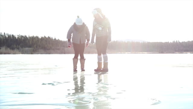 Two middle aged women have fun on frozen lake together