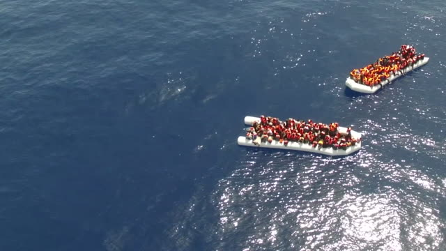 two migrant boats float off the italian coast before rescue 2017 - flüchtling stock-videos und b-roll-filmmaterial