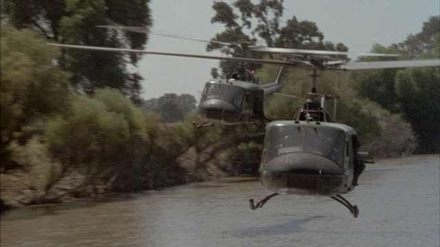 Two military helicopters fly over a river in Vietnam.