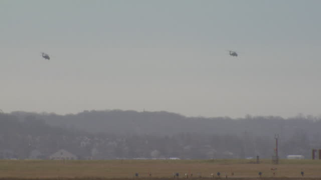 two military helicopters flying over airport, usa - kampfhubschrauber stock-videos und b-roll-filmmaterial