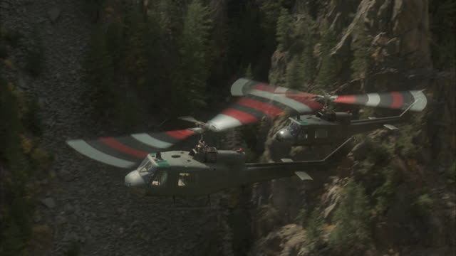air to air, ms, two military helicopters flying over mountains - military helicopter stock videos and b-roll footage