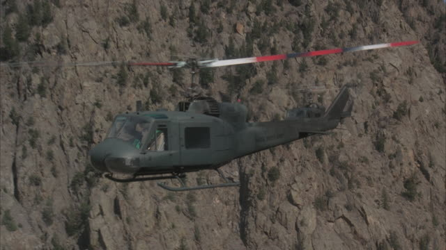 air to air, ms, two military helicopters flying over rocky mountains - us military stock videos & royalty-free footage